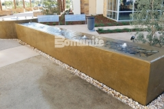 Featured here is Bomanite smooth-troweled, integrally colored concrete that was used to create a stunning water feature that enhances the tranquil and therapeutic design aesthetic in this outdoor space.