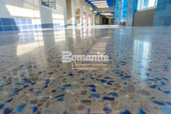 A Bomanite Modena SL topping slab was installed here to renovate the entrance hallway at Grain Valley High School and the incorporation of two shades of vibrant blue glass aggregate and eye-catching pieces of sparkling mirror glass combined with the custom polishing process created a unique and radiant flooring surface that embodies the school's colors and team spirit.