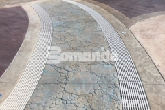 Bomanite imprinted concrete was expertly installed here by our colleague, Harrington Bomanite, including these serpentine drains that were incorporated into the hardscape to infiltrate storm water and minimize runoff while accentuating the decorative concrete decking.