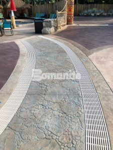 Close up of winding wateway concept of decorative concrete drainage system at Canobie Lake Park Castaway Island Expansion using Bomanite Imprint Systems and multiple Bomacron Patterns displays award winning craftsmanship.
