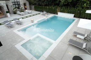 Overhead view of pool deck and firepit seating area using the Bomanite Sandscape Refined Exposed Aggregate System with bands of grass installed by Bomanite Toronto in Canada.